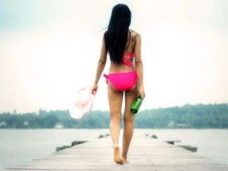 Frau im Bikini auf einem Steg