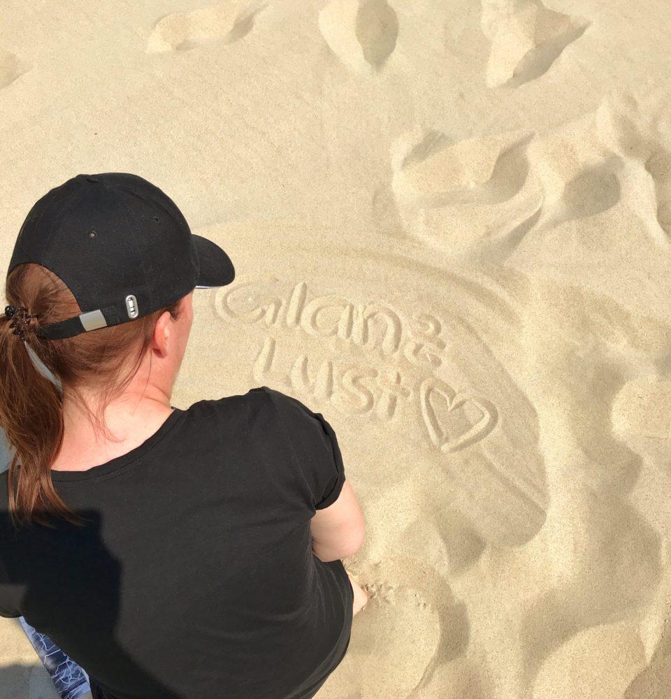 Katy Glossy Glanzlust Schrift im Sand geschrieben